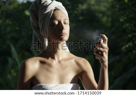 Woman spraying facial mist on her face, summertime skincare concept Royalty-Free Stock Photo #1714150039