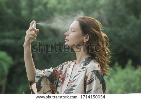 Woman spraying facial mist on her face, summertime skincare concept Royalty-Free Stock Photo #1714150054