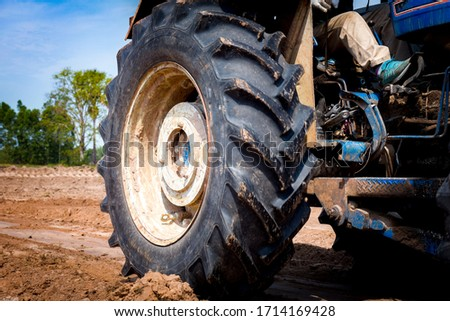The tractor wheels on the huge field, a farmer riding a tractor, a tractor working in a field agricultural machinery in the work, tractor in the background cloudy sky #1714169428