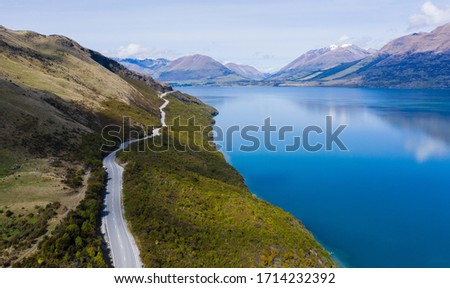 Aerial view of Lake Wakatipu and surrounding mountains on a sunny spring day near Glenorchy in New Zealand. forest and trees lean the lake and white mountain. A peaceful picture