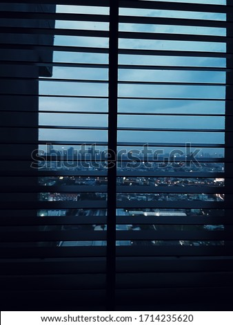 Night fall view of large window with Venetian blinds. View overlooking city skyscrapers and cloudy sky conveys sad, lonely and desperate feeling. #1714235620