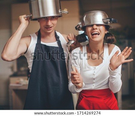 Couple in love. Funny photo. Happy day. Photo of funny male chief in white uniform holding rolling pin while standing at kitchen in restaurant. People. Smile woman. Romantic lovers. Fun. Idea.