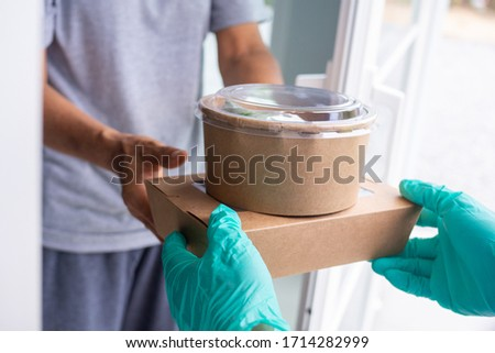 Deliveryman wears the gloves and the mask. Send cardboard boxes containing food to online shoppers. Fast delivery of products or food during detention home. Reduce covid-19 virus outbreaks #1714282999