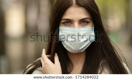 COVID-19 Pandemic Coronavirus Woman on city street wearing face mask protective for spreading of disease virus. Girl with protective mask on face against Coronavirus Disease 2019. #1714284022