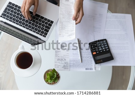Above top view close up young woman holding utility bills or receipt, managing monthly expenses with e-banking application on computer, professional accountant or bookkeeper doing paperwork indoors. Royalty-Free Stock Photo #1714286881