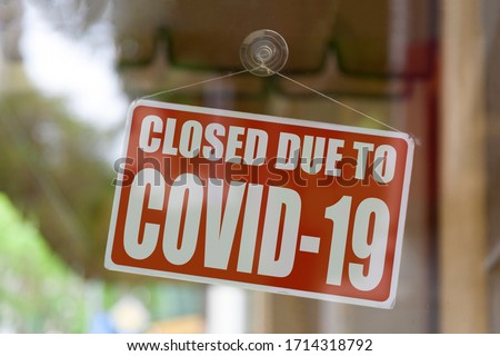 "Close-up on a red closed sign in the window of a shop displaying the message ""Closed due to Covid-19"". #1714318792"
