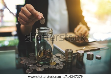 Closeup image of a businesswoman calculating, stacking and putting coins in a glass jar for saving money and financial concept #1714347379