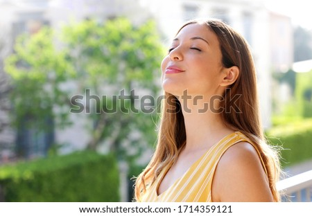 Relaxed young woman breathing fresh air on balcony in the morning Royalty-Free Stock Photo #1714359121