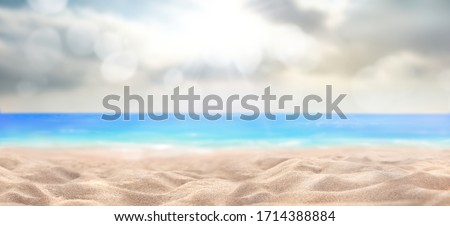 A summer vacation, holiday background of a tropical beach and blue sea and sun breaking through clouds.