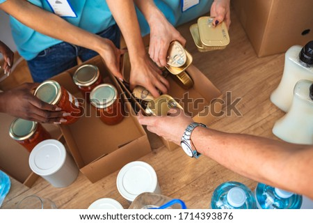 Small mixed race group of people working in charitable foundation. Generous people helping to poor people. People Donating Food To Charity Food Bank Collection In Community Center #1714393876