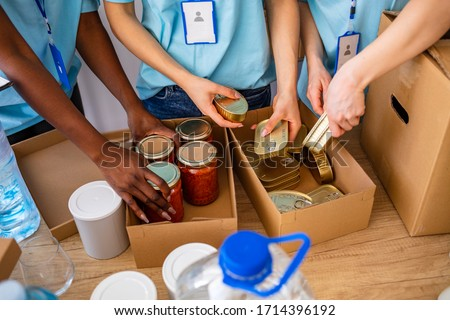 Homeless care. Charity team of volunteers putting food and drinks into paper box. Volunteers Collecting Food Donations In Warehouse. Volunteers with donation box with foodstuffs on wooden background #1714396192
