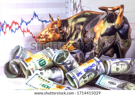 Concept of financial investment in bull market.  Copper bull near rolled one hundred us dollar bills. Stock market prices chart in background.