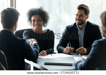 Smiling African American businesswoman shaking business partner hand at meeting, greeting each other, celebrating making good successful deal, signing contract, sitting at table in boardroom Royalty-Free Stock Photo #1714420771