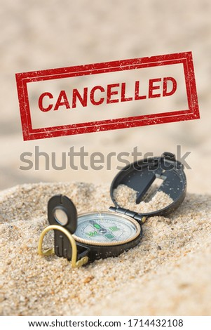 Cancelled stamp on a picture with a compass in a beach hot sand. Travel cancellation concept.