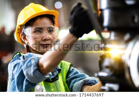 Woman worker wearing safety goggles control lathe machine to drill components. Metal lathe industrial manufacturing factory #1714437697