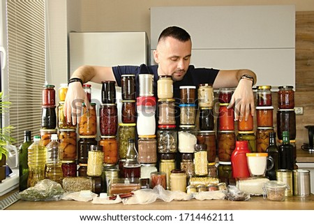attractive man with much food. victuals for eating in corona crisis. stay at home. fear of closed shops