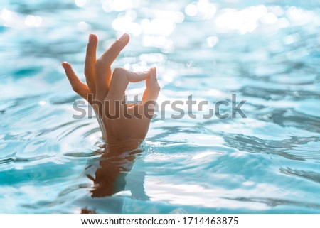 Woman hand make a sign, OK on the background of azure sea water and the glare of the sun. Female hand shows gesture OK. OK Hand sign.