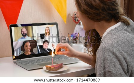 Woman celebrating her birthday through video call virtual party with friends. Lits and blows out candle. Authentic decorated home workplace. Coronavirus outbreak 2020. #1714470889