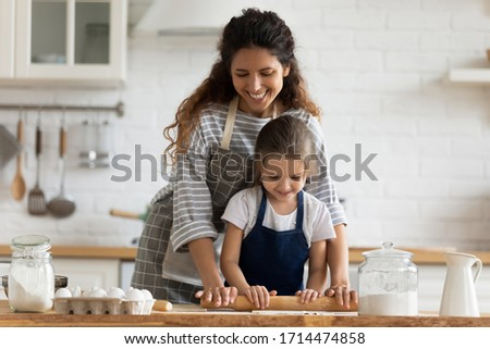 Happy attractive mommy helping cute smiling little preschool child daughter rolling dough for homemade pastry. Excited two female generations family enjoying cooking process together in kitchen. #1714474858