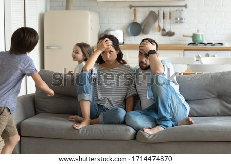 Stressed young parents sitting on couch, tired of crazy loud hyperactive little children siblings at home. Unhappy married couple irritated by naughty small kid son daughter, suffering from headache. #1714474870