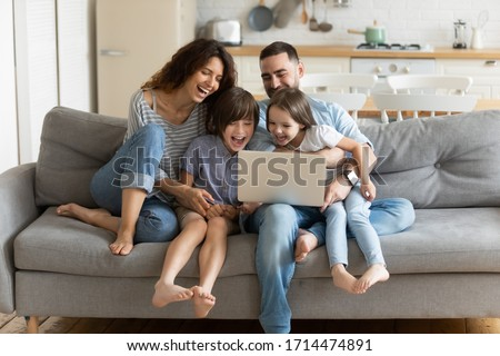 Overjoyed kids sitting on sofa with cheerful parents, watching funny video on computer. Happy married couple enjoying spending weekend time with small children, laughing looking at laptop screen.