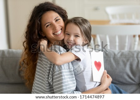 Head shot close up smiling cute little kid girl embracing young woman mother babysitter, congratulating with birthday or special event, preparing handmade greetings post card, looking at camera.