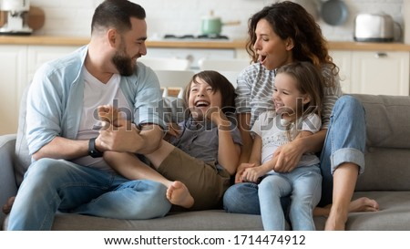 Happy young father tickling little kid boy son while smiling mother cuddling small daughter on couch. Cheerful full family of four having fun on sofa, enjoying weekend holiday time together at home. #1714474912