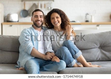 Smiling young bearded man sitting on sofa, cuddling attractive joyful wife, looking at camera. Happy family couple watching comedian movie funny video, enjoying holiday weekend time together at home.