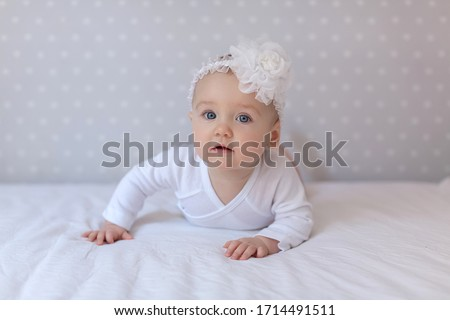 Cute baby in a white light bodysuit on the bed at home looking at the camera. Portrait of a cute baby lying down on a blanket. Baby girl smiling. Portrait of a crawling baby on the bed in her room. #1714491511