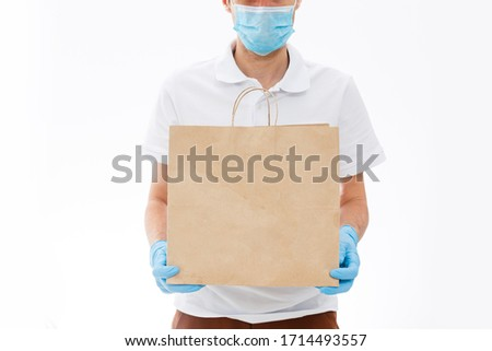 Courier in protective mask and medical gloves delivers takeaway food. Delivery service under quarantine, disease outbreak, coronavirus covid-19 pandemic conditions. #1714493557