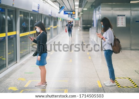 Two young asian woman wearing protective face mask stand in line with social distancing during waiting train in subway due to Coronavirus or COVID-19 outbreak situation in all of landmass in the world #1714505503