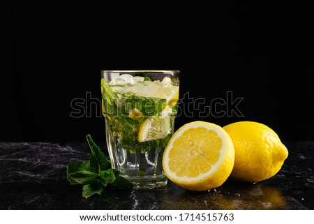 glass of mojito decorated with a sprig of mint and lemons on a dark background. close horizontal picture #1714515763