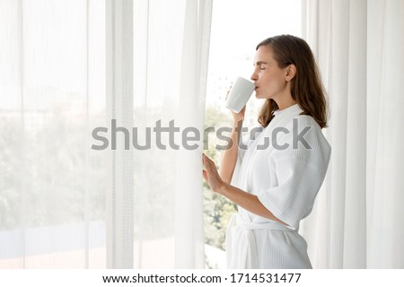 Beautiful Young Caucasian woman in pajamas holding a glass of white coffee ready to drink by the window in the bedroom at home after wake up in the morning. Woman standing drinking coffee by window. #1714531477