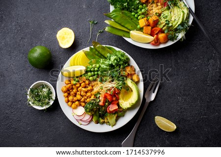 Healthy vegetarian lunch bowl with avocado, chickpeas, quinoa and vegetables, garnished with microgreens and nut dressing. Flat lay on dark concrete background. #1714537996