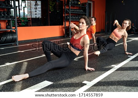 Group of young adult athletic people training in animal flow style, making kick to the side, spending workout session together with personal coach in gym club Royalty-Free Stock Photo #1714557859