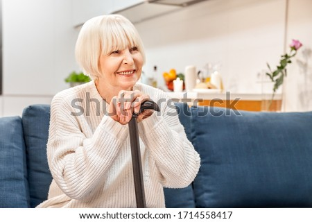 Happy elderly woman with walking cane in hands spending weekend at home, sitting on couch in living room, looking aside, making beaming smile #1714558417