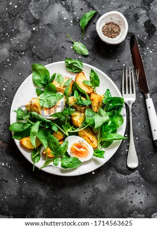 Baked potato, boiled egg and fresh spinach salad on dark background, top view. Delicious breakfast, snack    #1714563625