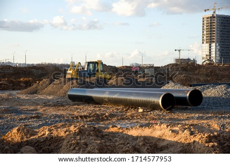 Bulldozer during construction of main water supply pipelin and natural gas. Laying underground storm sewers at construction site. Water main sanitary drainage system . Dozer for land clearing #1714577953