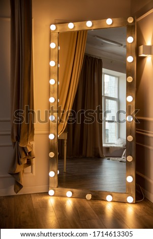 A large mirror with lighting against the wall in the room. Yellow light lamps around the perimeter of the frame. Convenient mirror for applying makeup. #1714613305