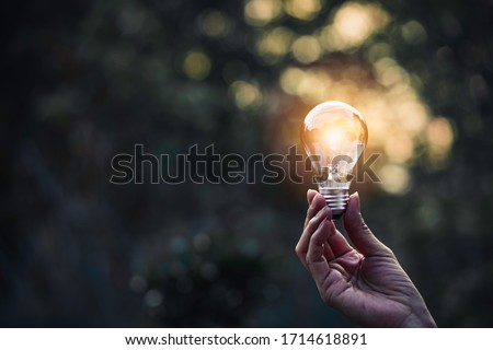 Innovation and energy concept of hand hold a light bulb and copy space for insert text. Royalty-Free Stock Photo #1714618891