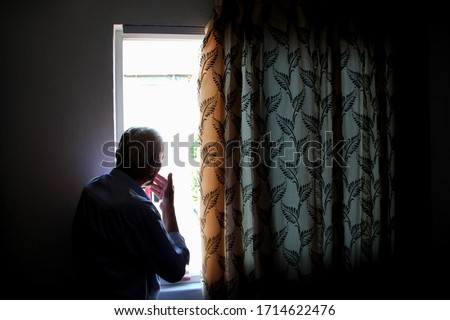 Elderly man indoors in the house looks out the window. Loneliness.  Corona virus. Stay at home, stay safe Royalty-Free Stock Photo #1714622476