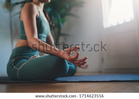Morning Mindfulness Meditation, Closeup of young woman practicing yoga in the morning sitting straight and comfortable on yoga mat, blank space for text or content #1714623556
