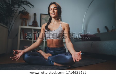 appy young sportive woman meditating at home in the morning practicing yoga, Wellness concept, Woman breathing doing Ardha Padmasana exercise sitting indoor in lotus pose with mudra gesture #1714623652