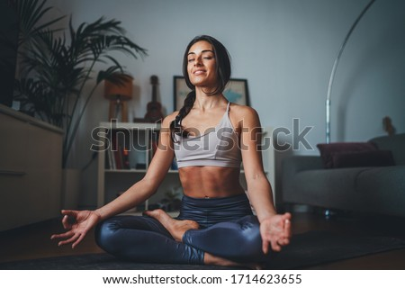 Beautiful hispanic woman practicing mindfulness yoga at home sitting on yoga mat smiling happy with closed eyes breathing fresh air enjoy peace of mind no stress free #1714623655