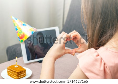 Young woman celebrates birthday during quarantine. Virtual birthday party online with her friend or lover. Video call on tablet. Social distance, stay at home, self-isolation. Selective focus #1714627165