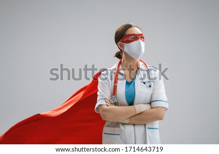 Doctor wearing facemask and superhero cape during coronavirus outbreak. Virus and illness protection, quarantine. COVID-2019. Super hero power for  medicine. #1714643719