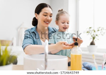 A cute little girl and her mother are washing their hands. Protection against infections and viruses.    #1714643749
