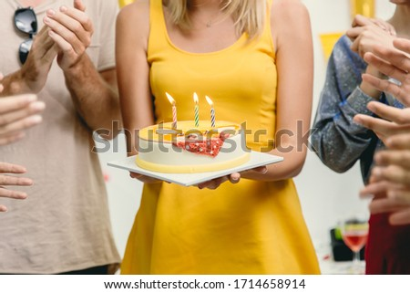 Closeup woman with birthday cake in the party around with friends clap her birthday celebration song.
