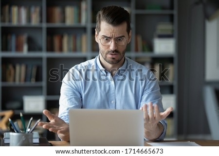 Unhappy shocked man having problem with broken or discharged laptop, looking at screen, amazed guy wearing glasses reading bad news in email, stressed businessman surprised by financial report #1714665673