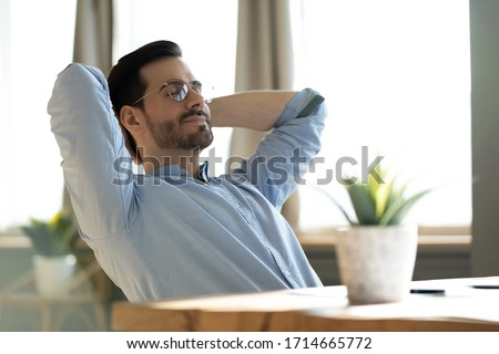 Peaceful young man wearing glasses daydreaming with closed eyes, lazy sleepy businessman or student leaning back in comfortable chair, stretching hands, sitting at work desk, dreaming and visualizing Royalty-Free Stock Photo #1714665772